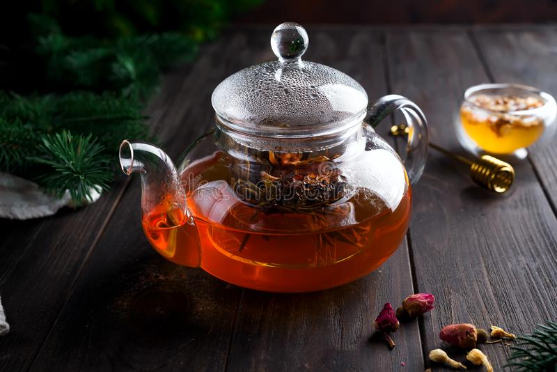 Glass teapot with freshly brewed herbal tea and honey on a wooden background. Christmas or hot winter drink to warm. stock images