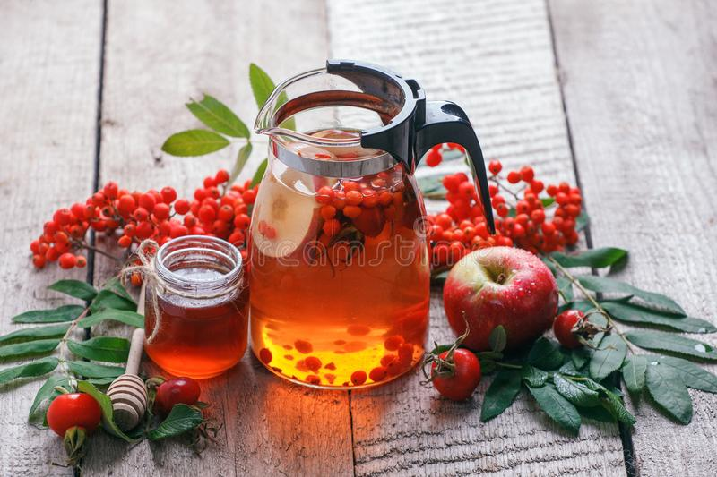 Glass teapot with hot beverage - berry apple citrus honey tea. Vitamins for autumn, winter. Immunity treatment for cold fall days. Traditional medicine stock photos