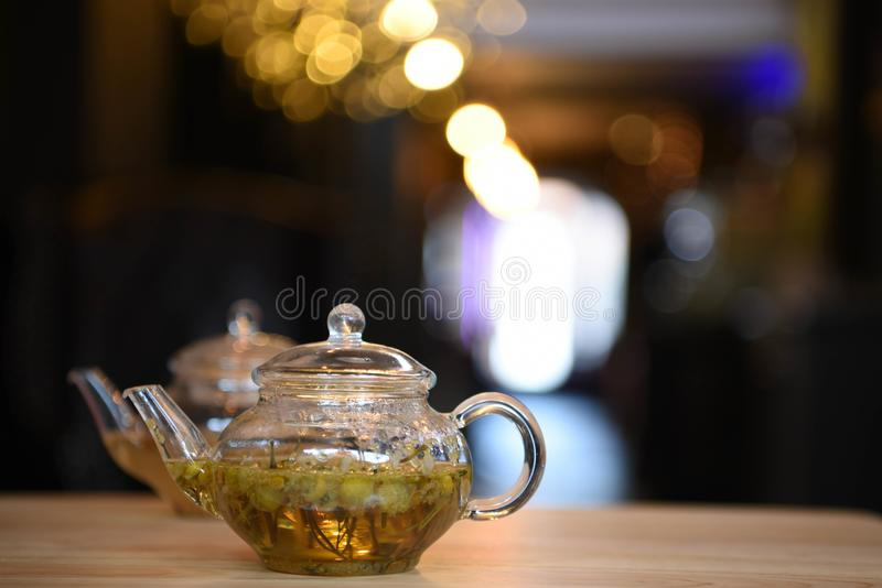 A glass teapot filled with hot camomile tea in yellow and green colors with bokeh blur lights in a kitchen background. A glass teapot of hot tea made with floral stock image