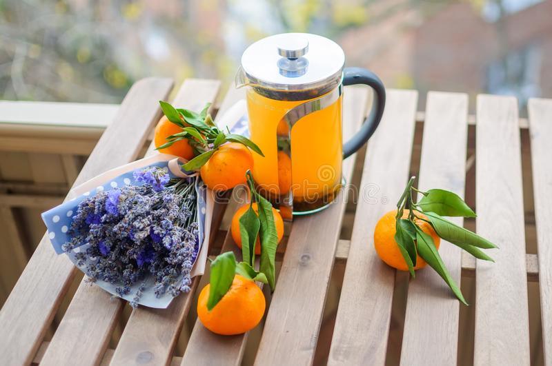 Glass teapot, tangerines and bunch of dry flowers. Close up beautiful natural stillife of several fresh tangerines, vitamin drink in kettle and violet flowers stock photography