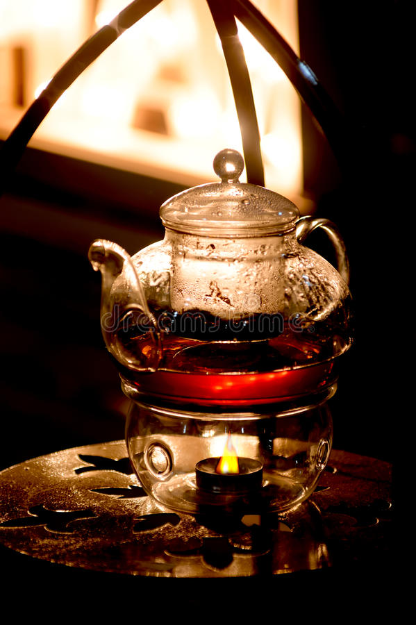 Glass teapot for tea making. Heating from a candle stock photography