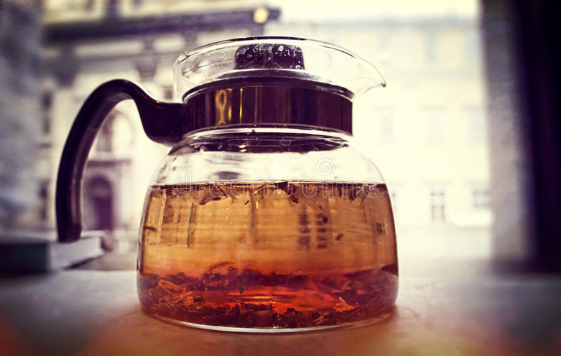 Glass teapot at the window. In a warm light royalty free stock photos