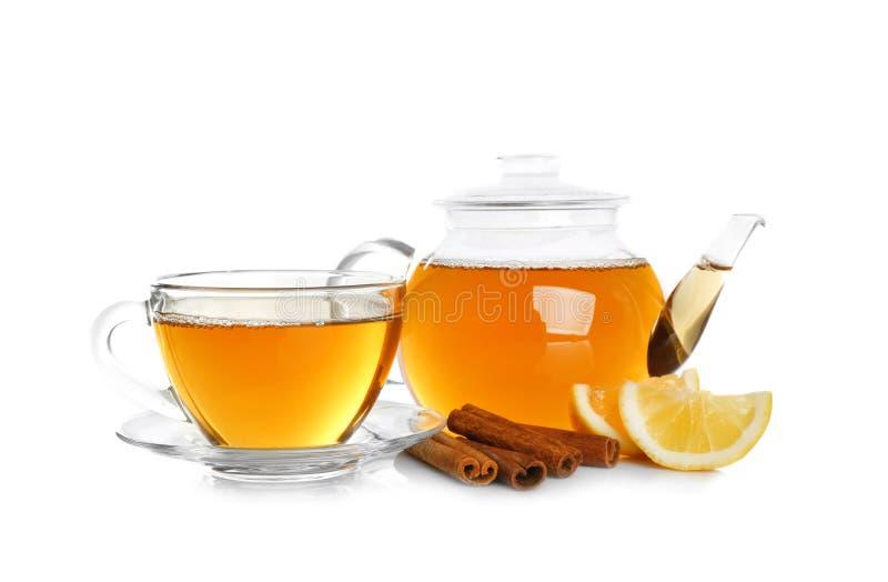 Glass tekanna och kopp med aromatiskt varmt kanelbrunt te arkivbild