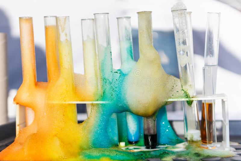 Glass test tubes with liquid in it and colorful foam in science research lab. Failed experiment concept royalty free stock photography