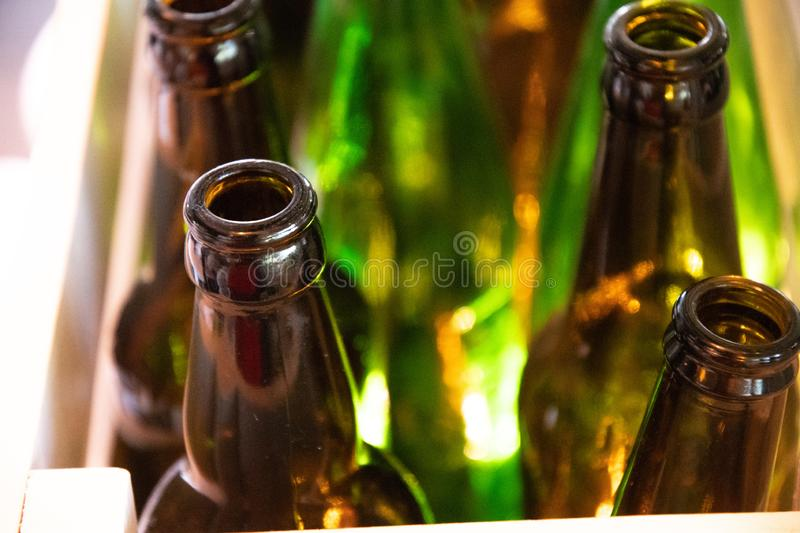 Empty bottle glass bottlenecks closeup. Polished clean glass texture of retro shaped beer bottles. Glowing transparent surface royalty free stock image