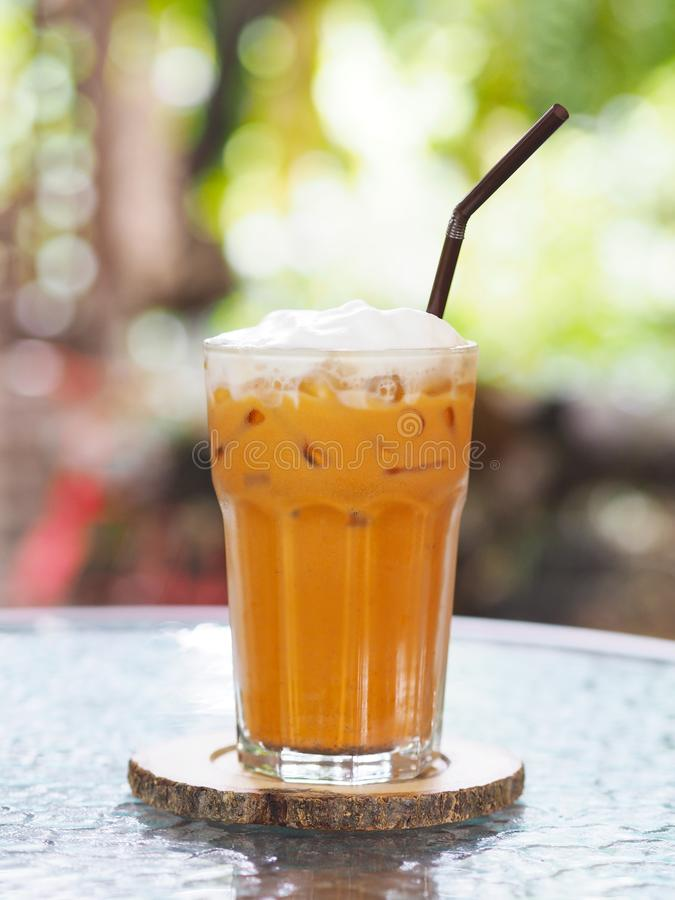 Glass of Thai milk tea with whipped cream on top and straw at cafe royalty free stock photography