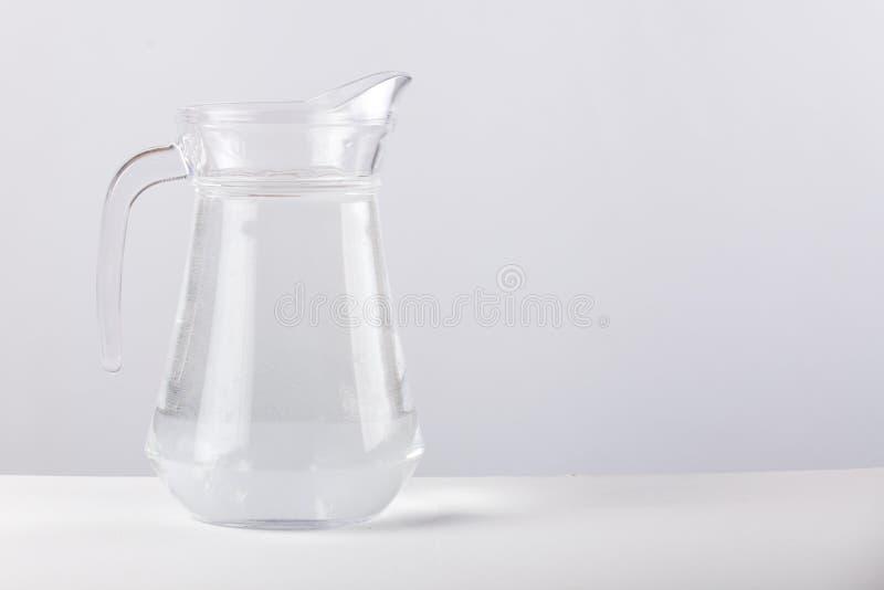 Glass tillbringare med vatten som isoleras på vit bakgrund arkivbild