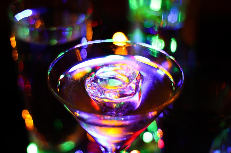 Glass to view on cocktail glass with ice cube in vibrant colors. Colorful bright magic bokeh background stock images