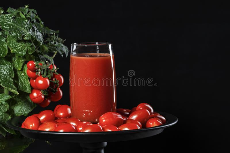 Glass of tomato juice covered with cherry tomatoes comes from a natural tomato bush, conceptual image stock images