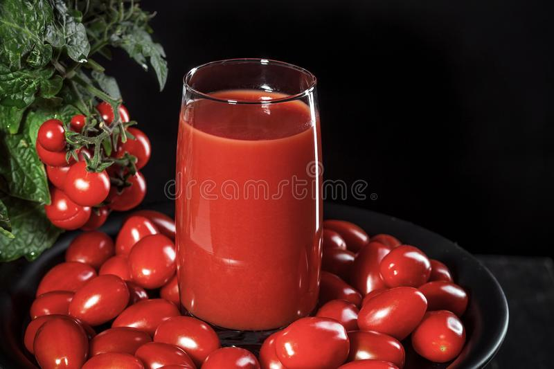Glass of tomato juice covered with cherry tomatoes comes from a natural tomato bush, conceptual image stock image