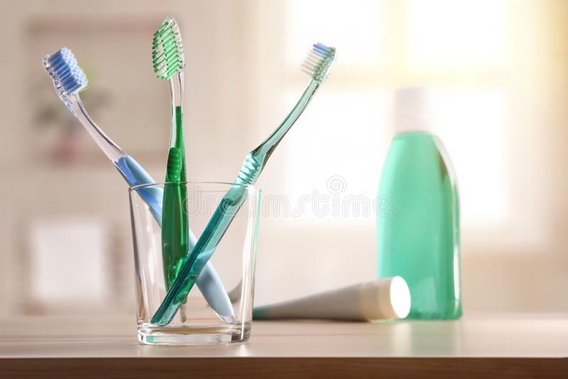 Glass with toothbrushes on wood table in bathroom general composition. Glass with toothbrushes on wood table in bathroom. Horizontal composition. Front view royalty free stock images