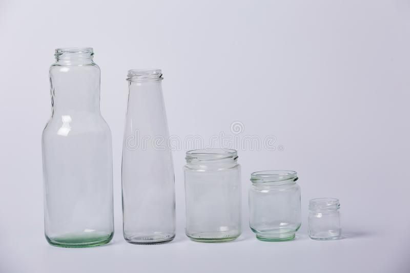 Glass transparent bottles.Glass transparent bottles of different sizes from large to small on a white background. stock photo