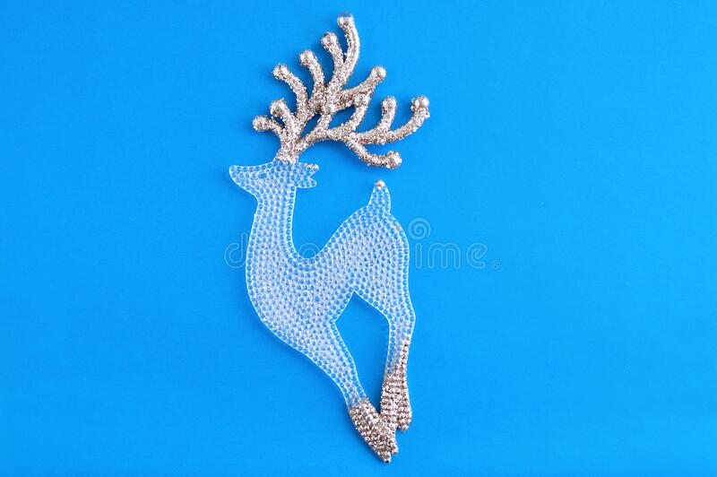 Glass transparent figurine of a deer with golden sparkles horns on blue background. Glass transparent figurine of a deer with golden sparkles horns on a blue royalty free stock photo