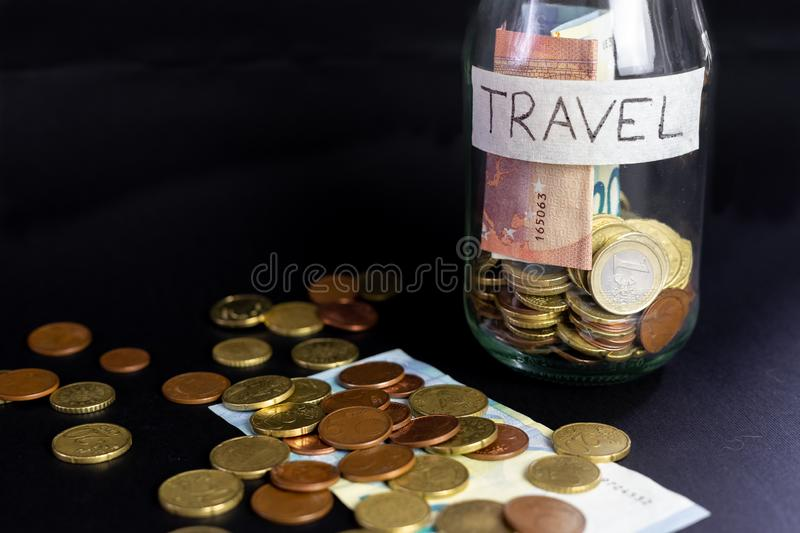 Glass transparent jar labeled handwritten travel. Euro Banknotes and coins inside and outside of the jar.  black backgroun stock photography
