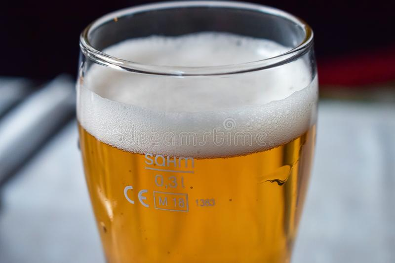 Glass transparent glass with light beer with a large layer of foam. Glass transparent glass with beer with a large layer of foam royalty free stock photos