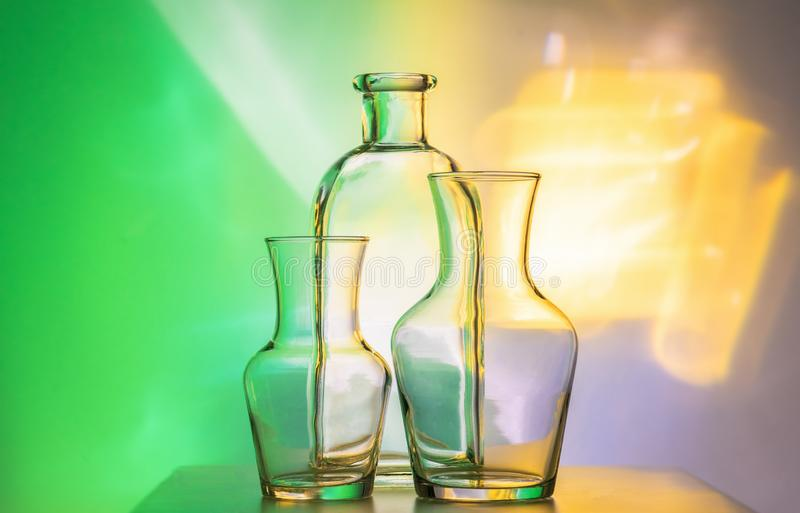 Glass transparent tableware - bottles of different sizes, three pieces on a beautiful multi-colored, yellow, and green royalty free stock photography