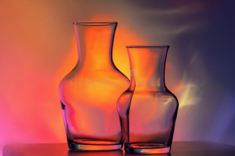 Glass transparent tableware - bottles of different sizes, three pieces on a beautiful multi-colored, yellow, lilac and royalty free stock images