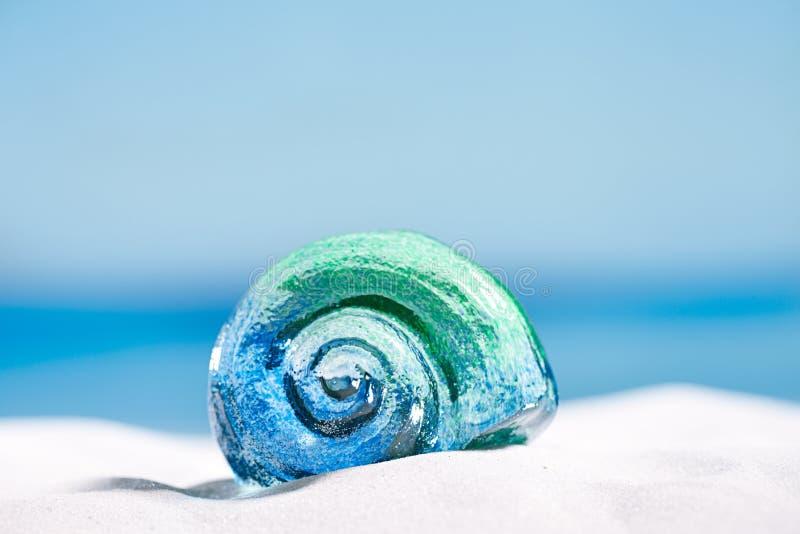 Glass tropical sea shell on white beach sand under the sun lig. Ht, shallow dof royalty free stock photo