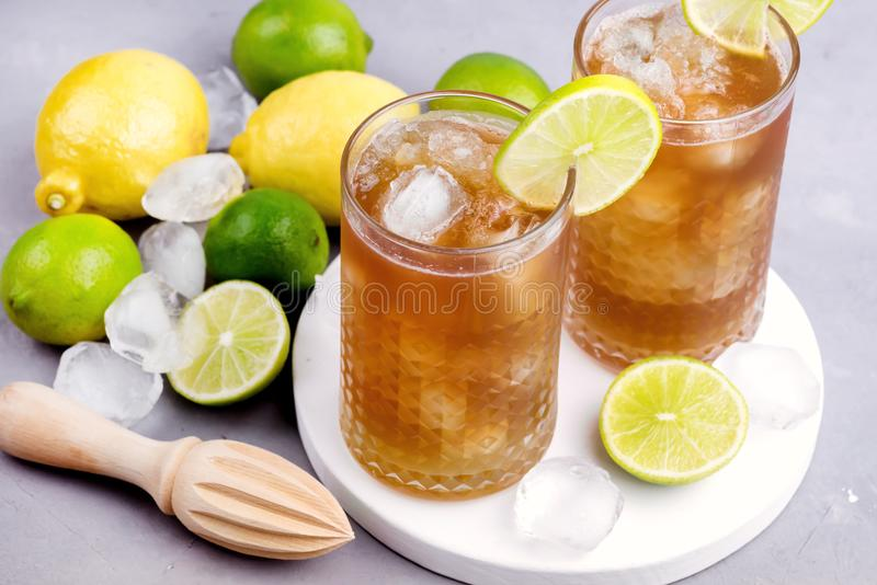Glass of Tsasty Ice Tea with Ice Cubes and Citrus Cold Summ er Beverage Wooden Squeezer and Raw Lemons and Limes on Background royalty free stock image