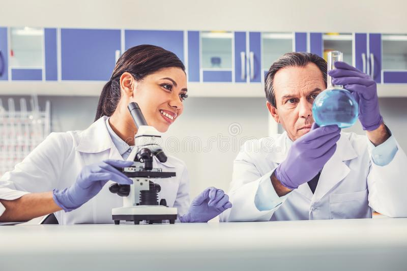 Professional biologist showing glass tube to his assistant stock image