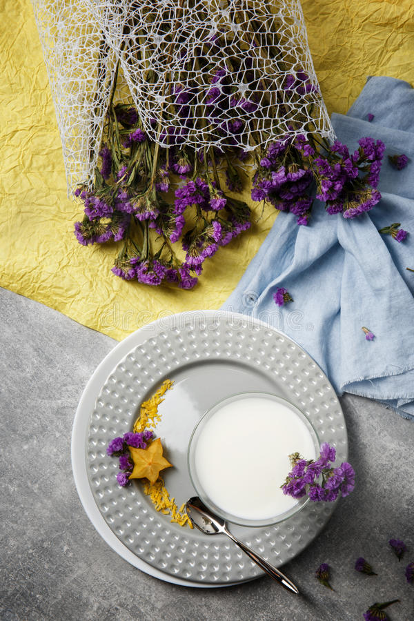 A glass of vanilla smoothie on a round plate.Blue and yellow fabric with purple flowers. A white milkshake on a gray stock photography