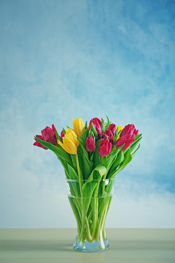 Glass vase with bouquet of beautiful tulips royalty free stock image