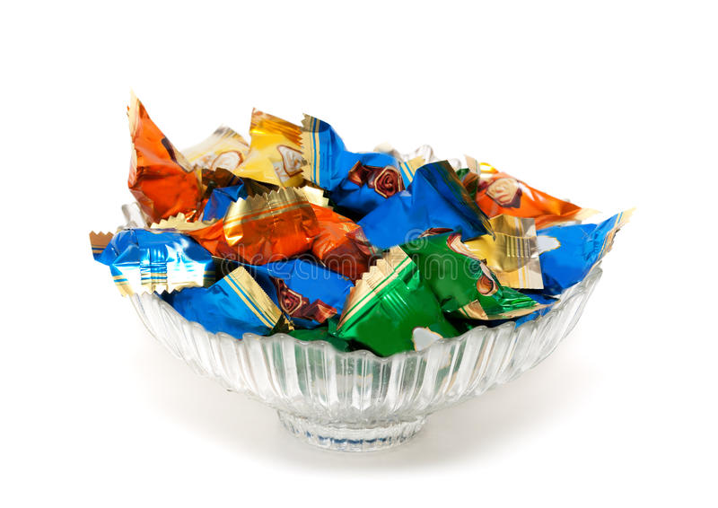 Glass vase with candy in colorful wrappers stock photos