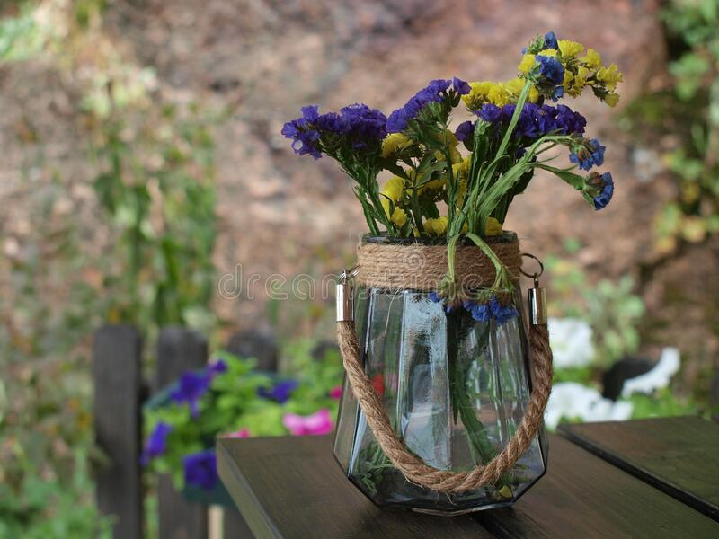A glass vase decorated with twine stands on a brown wooden table with purple and yellow flowers. Against the background of a large stone, fence and flowers stock photography