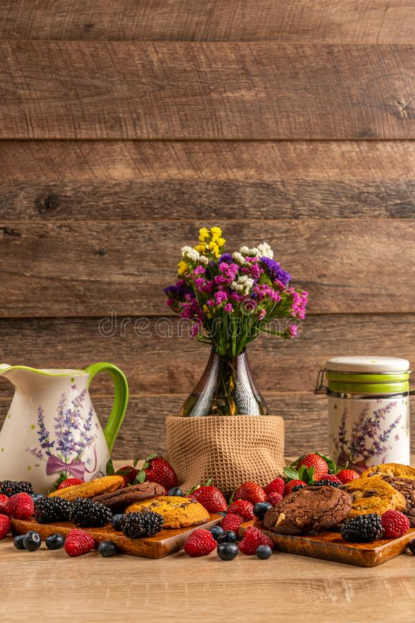 Glass vase with wild berries and chocolate biscuits on wooden board stock photo