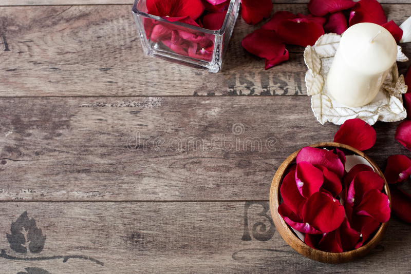 Glass vase and wood bow filled with red and white rose petals, white aromatic vanilla candle. Wooden background. Aromatherapy stock photo