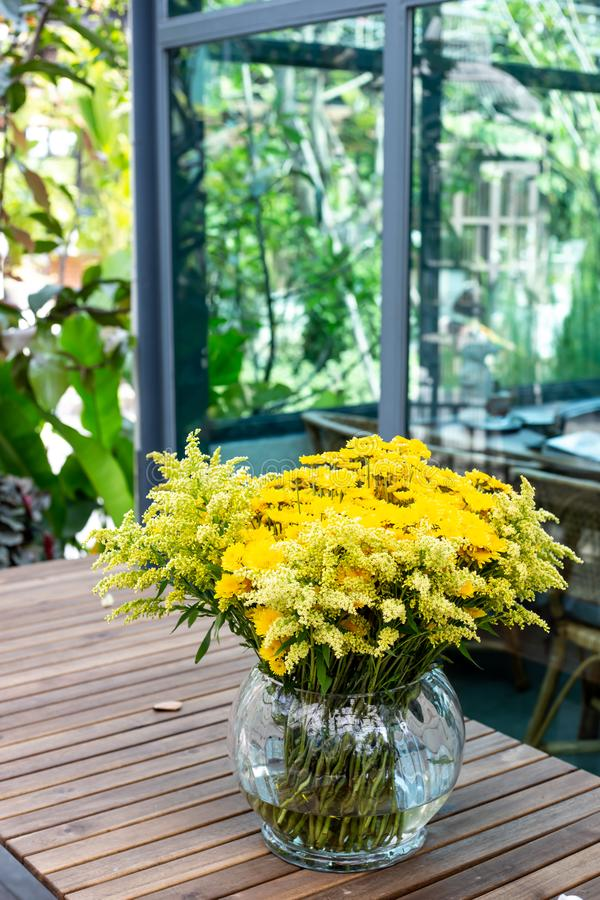 Glass vase with yellow flowers stock photo