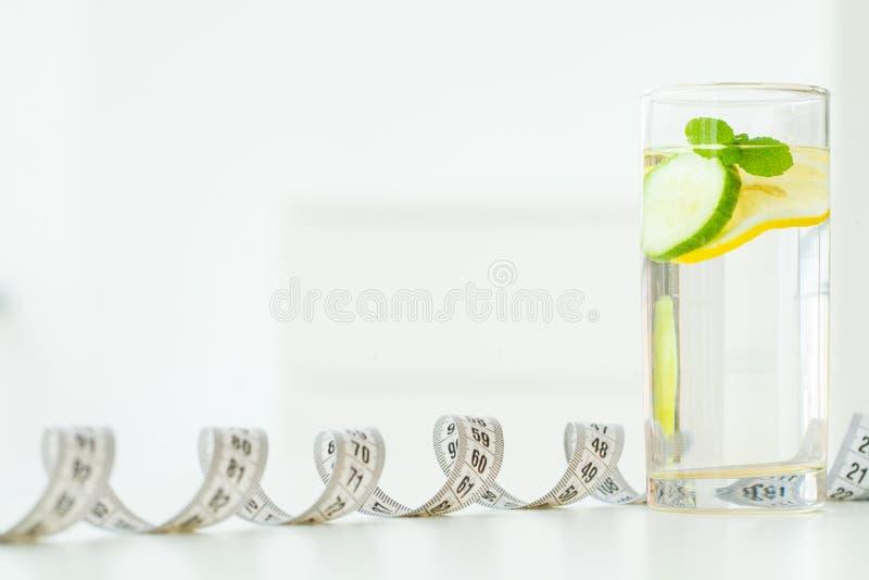 Glass vatten med mintkaramellsidor, citronen och gurkan, måttband - arkivbild