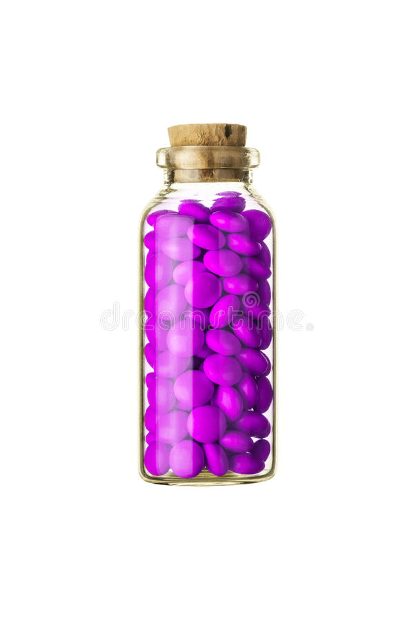 Glass vial full of small magenta pills stock images