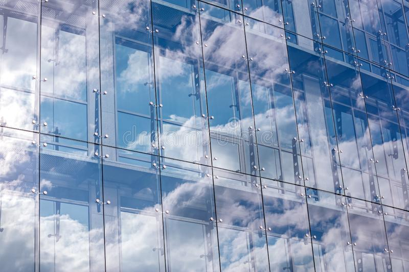 Glass wall of modern office building with cloudy sky reflection royalty free stock photos