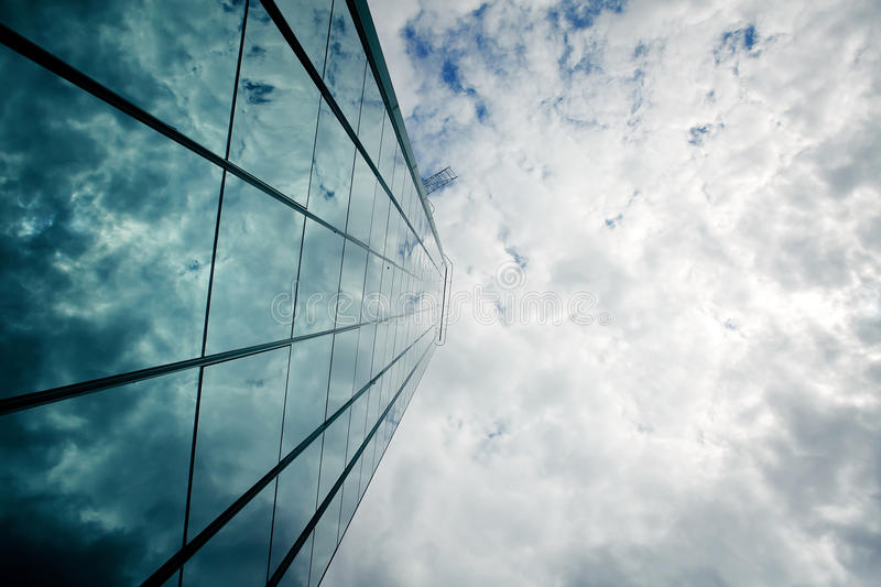 Glass wall of a skyscraper and a sky. Blue glass wall of a skyscraper and clouds royalty free stock photos