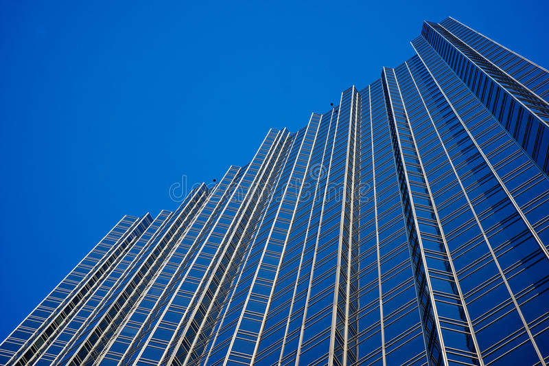 Glass Wall of Skyscraper. Glass and steel wall of a skyscraper towers into the blue sky stock photo