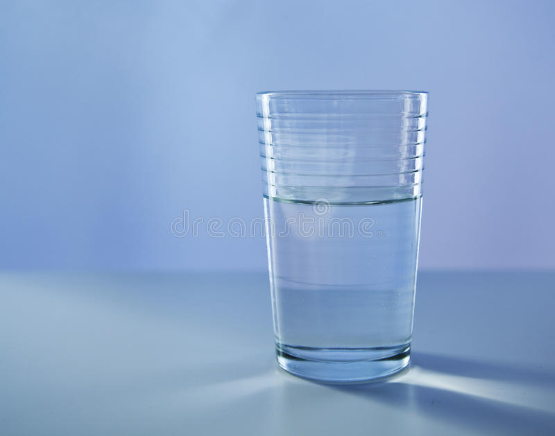 Glass of water. One glass of water standing on a blue background royalty free stock photo