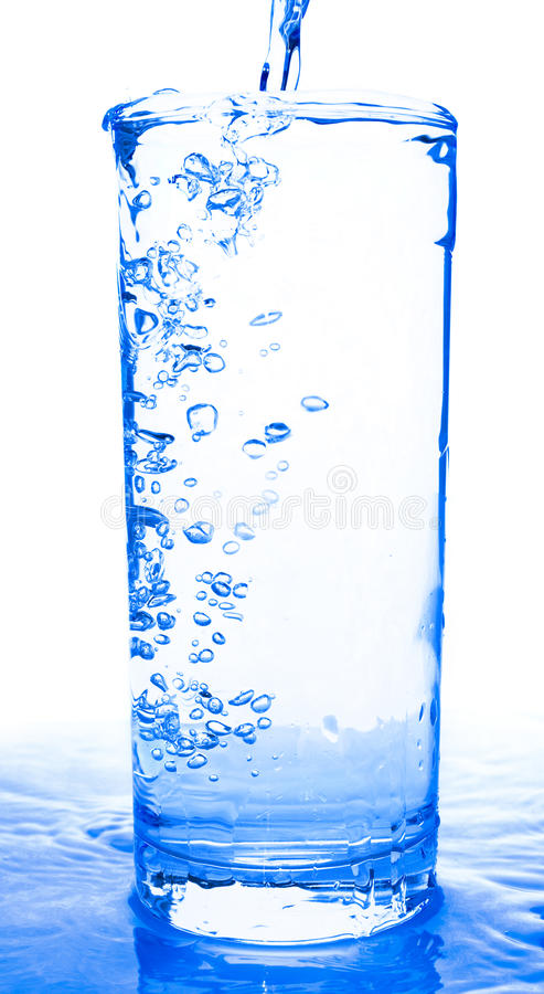 Glass of water. Being poured royalty free stock photos