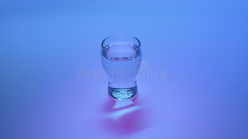 Glass of water on the color background stock image