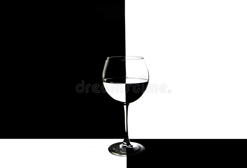 Glass with water on double colored background. Wine glass on two colored background black and white. Reflection in glass royalty free stock images