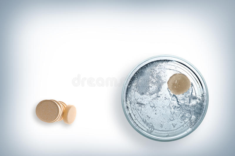 Glass of water with effervescent tablet top view. Glass of water with effervescent tablet and pile of pills on the table top view stock photo