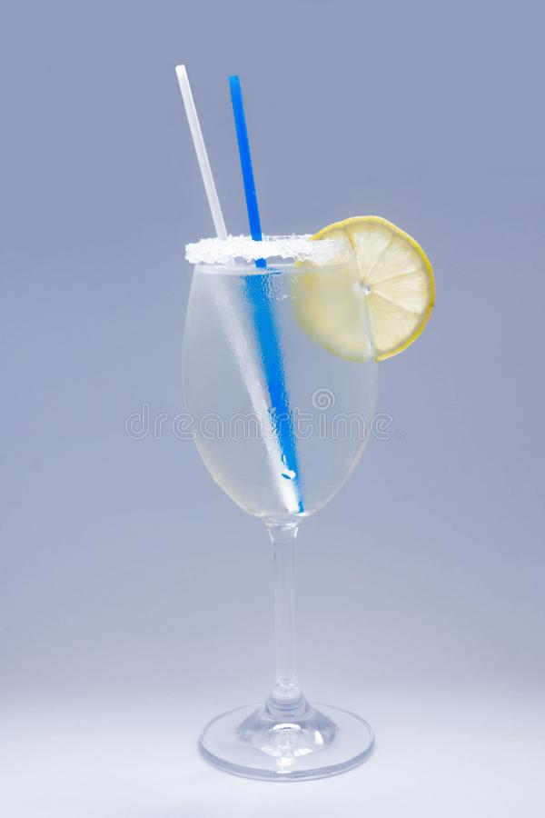 Glass of water grey background. Glass of water with lemon slice and straw sugar on glass royalty free stock photos