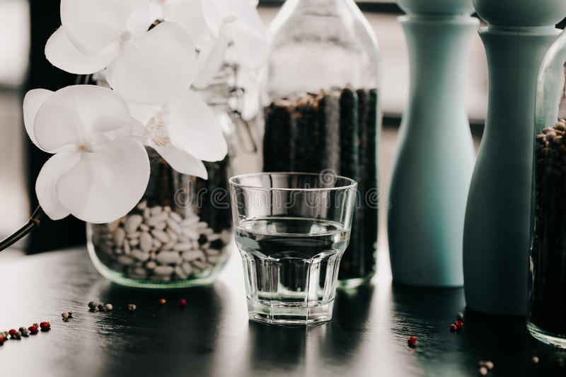 Glass of water. Healthy lifestyle. Flower blurred blackground. Fitness and Losing weight. Diet and Proper nutrition stock image