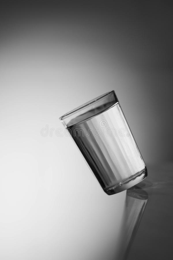 Glass of water. The inverted Cup. Glass of water on a dark background. Falling glass of milk. stock photography