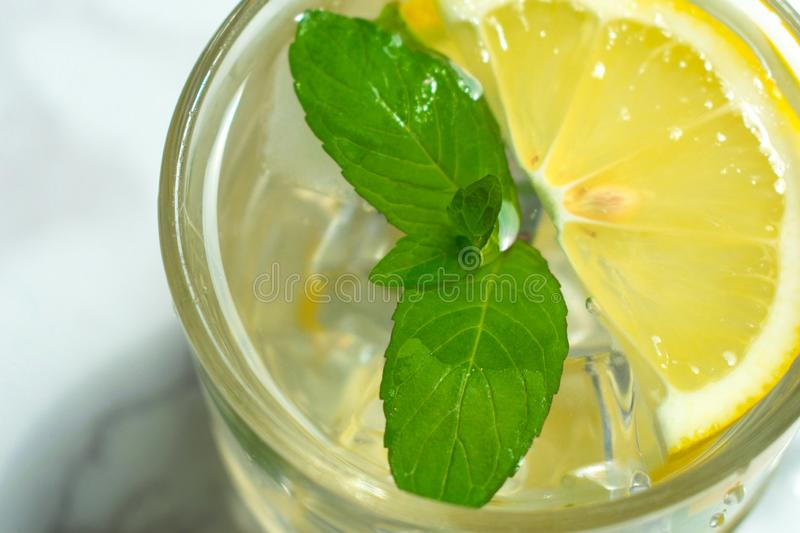 A glass of water with lemon and mint and ice. Cooling drink. stock images