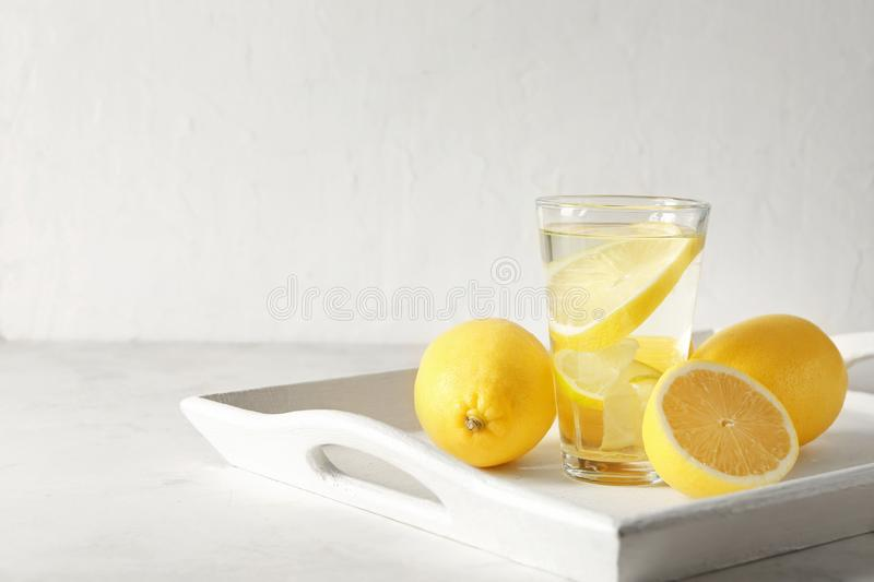 Glass of water with lemon on white tray stock images