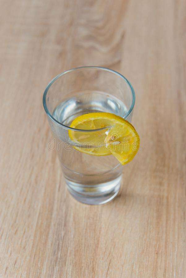 Glass with water and lemon on wooden table. Glass with water and lemon slice on wooden table, drink, refreshment, cold, fruit, lemonade, beverage, citrus stock photo
