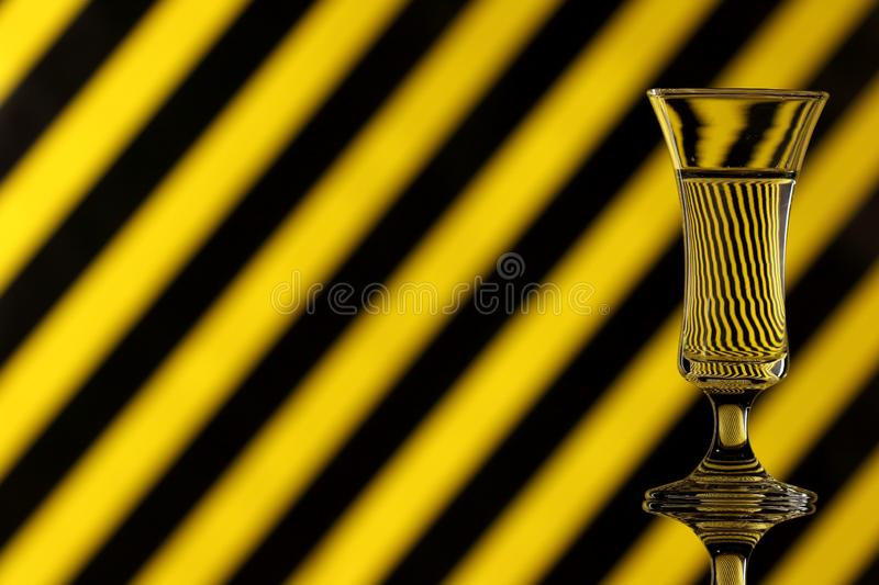 A glass of water on a multicoloured background showing refraction. Canvas wall art. A glass of water on a yellow and black striped multicoloured background stock image