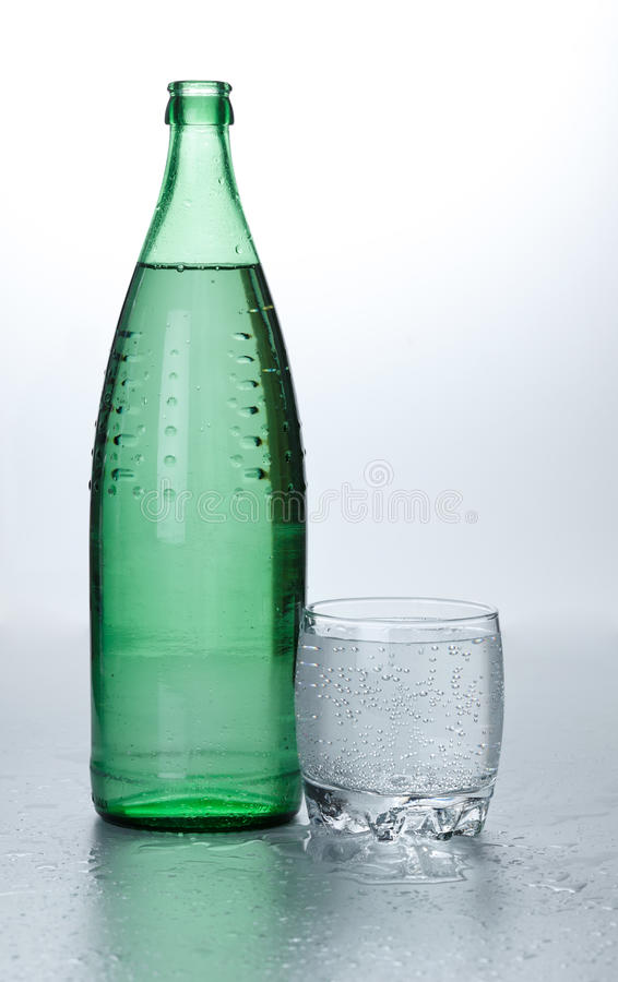 Glass of water near bottle stock photography