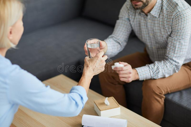 Glass of water for patient. Mature counselor passing glass of water to patient over table during discussion of his problems royalty free stock photos